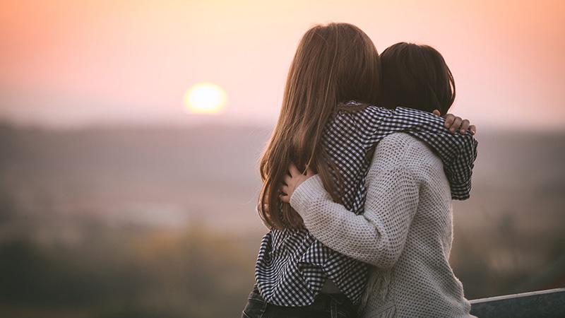 due bambine si abbracciano al tramonto