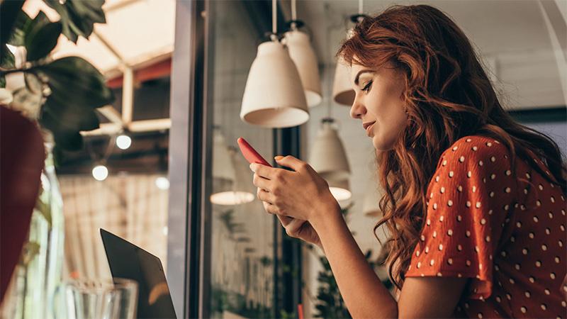 ragazza rossa guarda smartphone