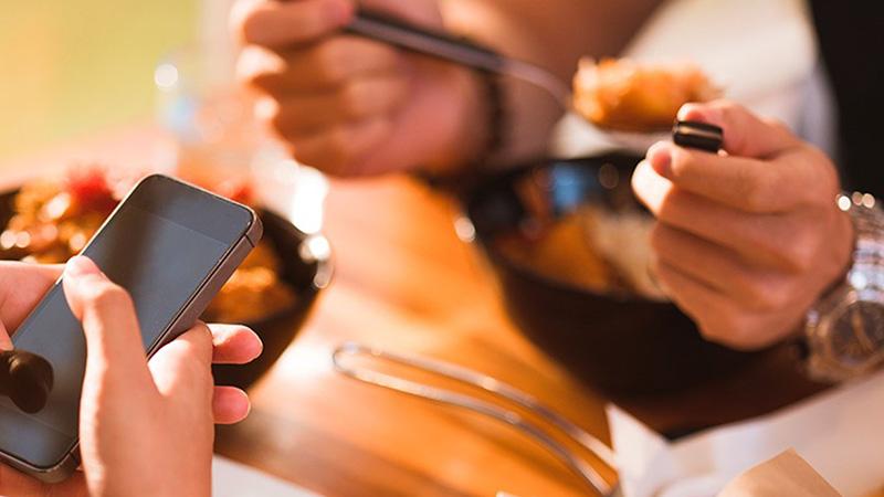 due persone a cena con smartphone